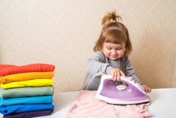 little funny housewife with iron. baby girl ironing baby clothes. a stack of bright clothes like a rainbow. Housewife helps mom