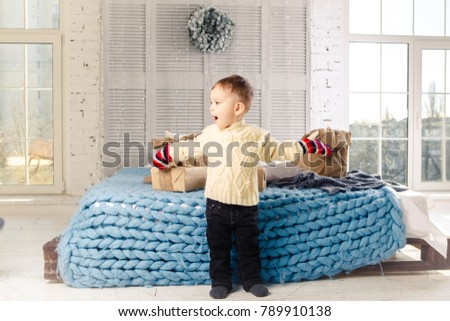 little funny playful boy a child sits on a bed on Christmas day with gift boxes in white wool knitted sweater and big bright mittens on it and laughs out loud. In interior there is a festive decor. #789910138