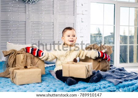 little funny playful boy a child sits on a bed on Christmas day with gift boxes in white wool knitted sweater and big bright mittens on it and laughs out loud. In interior there is a festive decor. #789910147