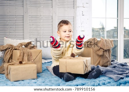 little funny playful boy a child sits on a bed on Christmas day with gift boxes in white wool knitted sweater and big bright mittens on it and laughs out loud. In interior there is a festive decor. #789910156