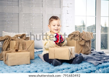 little funny playful boy a child sits on a bed on Christmas day with gift boxes in white wool knitted sweater and big bright mittens on it and laughs out loud. In interior there is a festive decor. #791683492