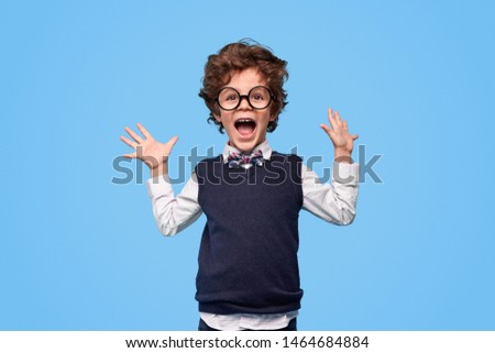 Little genius in nerdy glasses and school uniform yelling in excitement and holding hands up against blue background