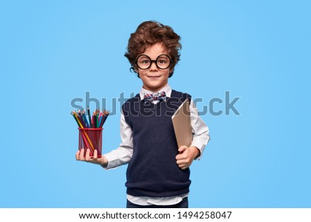 Little genius in round glasses and school uniform holding notebook and cup with pencils while standing against blue background during studies
