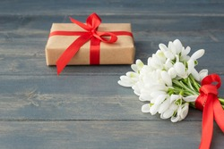 Little gentle bouquet of white snowdrops with red ribbon, wrapped gift box on dark wooden background. Copy space for text. Spring holidays, greetings concept.
