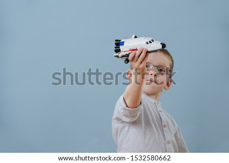 Little ginger boy in glasses plays with space shuttle lego model over blue background. He's absorbed in a process. He's imagining it flies past him. Half length. Foto d'archivio ©