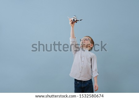 Little ginger boy in glasses plays with space shuttle lego model over blue background. He's absorbed in a process. He's moving it above his head and imagining it flies past him. Half length. Foto d'archivio ©