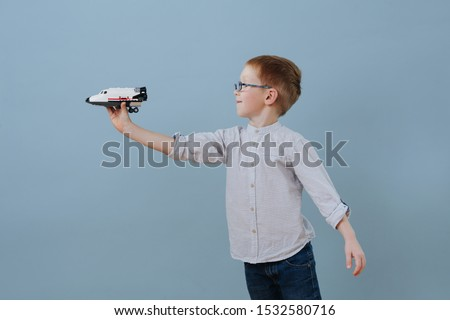 Little ginger boy in glasses plays with space shuttle lego model over blue background. He's absorbed in a process. He's imagining it flies past him. Half length. Side view. Foto d'archivio ©