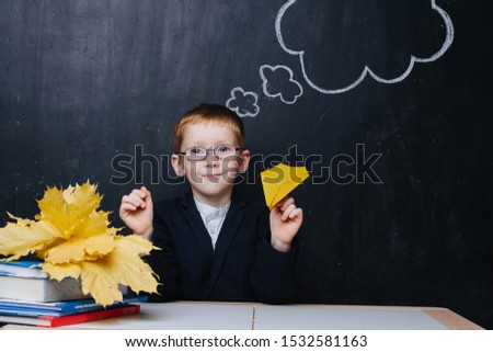 Little ginger boy is participating in a traditional first day of school portrait photo session. He sits behind the desk over blackboard. He holds paper plane with naughty expression on his face.
