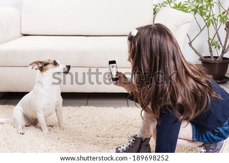 Little gir taking photo of her dog