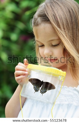 Little girl admires a Spicebush Swallowtail butterfly that she has captured.