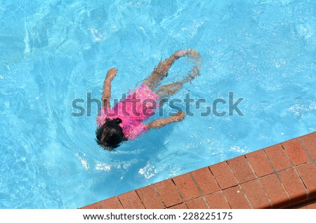 Little girl (age 04) swim in a swimming pool. top view