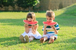 Little girl and a boy eating watermelon outdoors