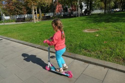 little girl, 4 and a half years old, plays with her scooter on a street in Sofia