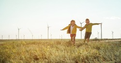 Little girl and boy are running in front of windmills. Renewable energies and sustainable resources - wind mills. children playing with the wind near a wind turbine
