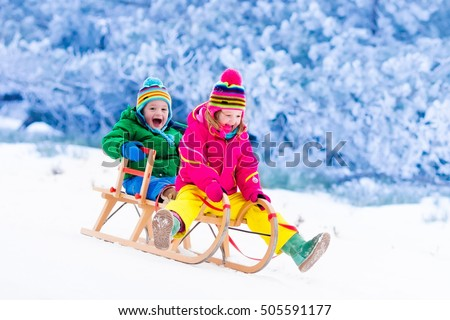 Little girl and boy enjoy a sleigh ride. Child sledding. Toddler kid riding a sledge. Children play outdoors in snow. Kids sled in Alps mountains in winter. Outdoor fun for family Christmas vacation. ストックフォト ©