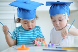 Little girl and boy in blue graduation hats paint colors at table