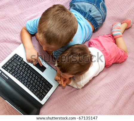 Little girl and boy lying in front of the monitor laptop at home on the couch. - stock photo
