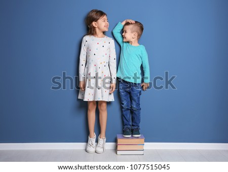 Little girl and boy measuring their height near color wall Stockfoto ©