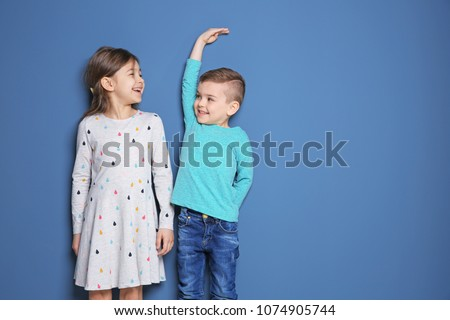 Little girl and boy measuring their height on color background