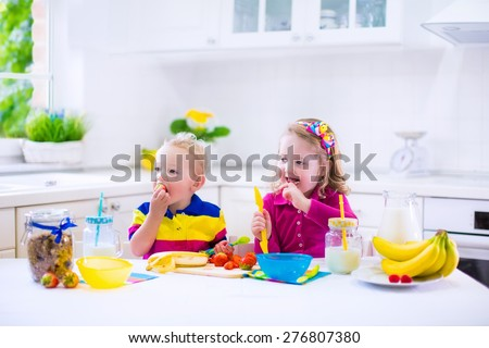Little girl and boy preparing breakfast in kitchen. Healthy food for children. Child drinking milk and eating fruit. Happy preschooler enjoying morning meal, cereal, banana, strawberry. Kids cooking