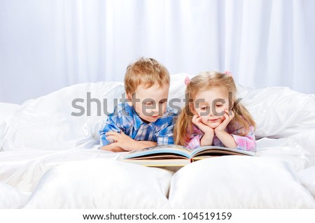 Little girl and boy read the book in the bed