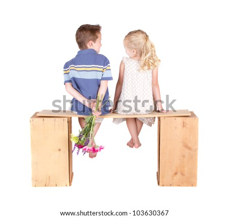 Little girl and boy sitting on a wooden bench holding flowers, isolated on white.