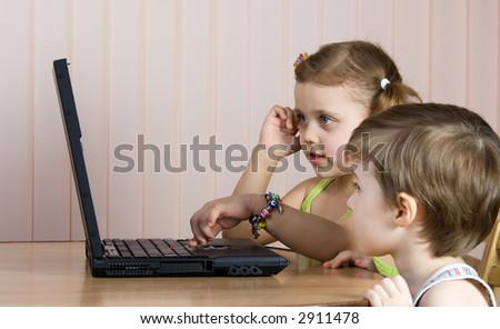little girl and boy working with a laptop