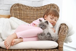Little girl and cat on wicker armchair in living room