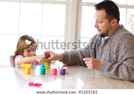 Little girl and father creating toys from playdough