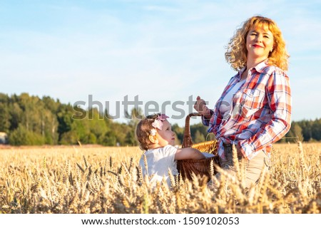 Little girl and girl with curly brown hair holds a wicker basket on a wheat field. Picnic in the countryside, countryside. #1509102053