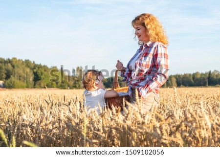 Little girl and girl with curly brown hair holds a wicker basket on a wheat field. Picnic in the countryside, countryside. #1509102056