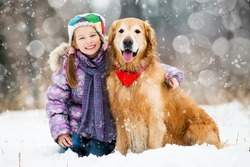 little girl and golden retriever looking at the camera