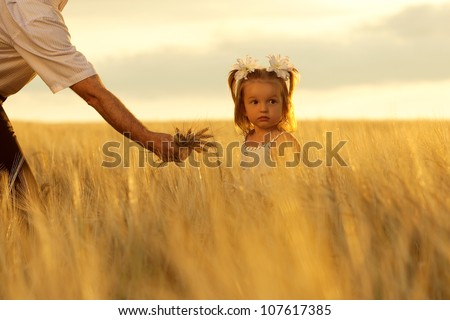 little girl and grandpa with a bouquet of wheat in the sunlight. outdoor shot