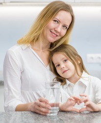 Little girl and happy mother with a glass of water on kitchen