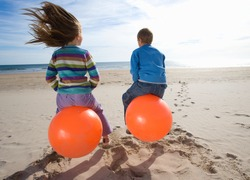 Little girl and her brother sitting on inflatable hoppers and bouncing on the beach on a bright, sunny day