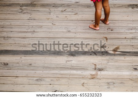 little girl and her footprint on wood plank
