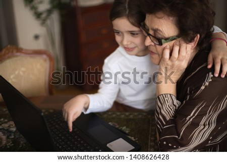 Little girl and her grandmother embraced sitting at the table, next to a laptop. Granddaughter points to her grandma's pictures and news on the Internet. Old woman of black hair looks at the laptop.