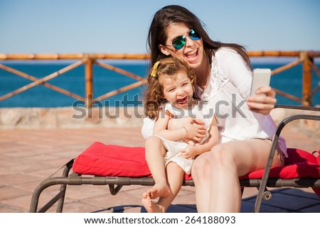 Little girl and her mom having some fun at the beach and taking a selfie with a smartphone #264188093