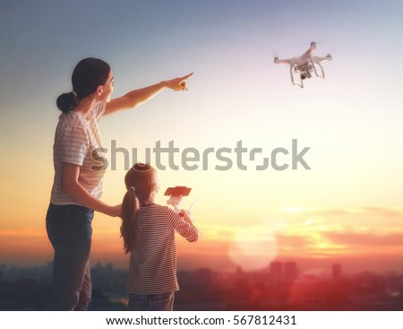 Little girl and her mother are operating the drone by remote control in the park. Kid and mom are playing with quadrocopter outdoors.  #567812431