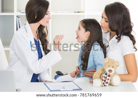 Little girl and her mother at pediatrician office. Doctor examine child's throat