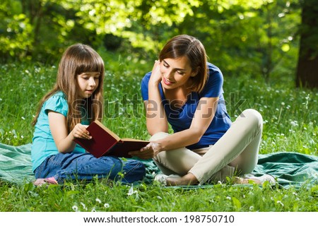 Little girl and her mother reading a book while they sitting and enjoy in beautiful nature,Mother and daughter reading a book
