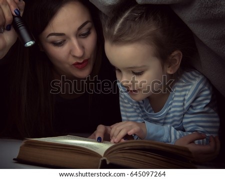 Little girl and her mother reading fairy tales book under the covers at the evening with lantern. Cute kid playing before going to sleep, image toned. Home family leisure. #645097264