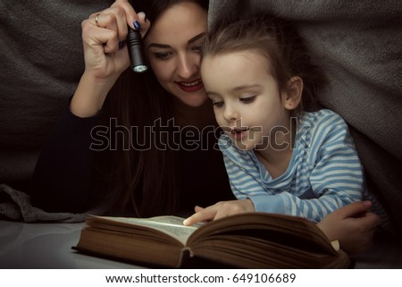 Little girl and her mother reading fairy tales book under the covers at the evening with lantern. Cute kid playing before going to sleep, image toned. Home family leisure. #649106689