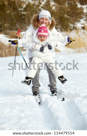 Little girl and her mother skiing in park
