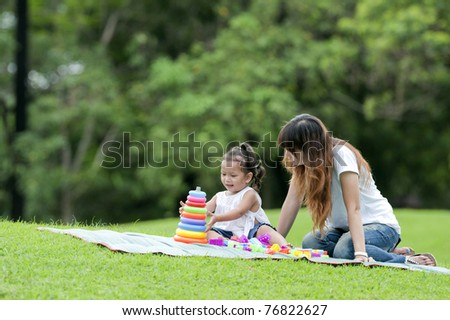Little girl and her mother were playing toys in the garden.