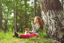 Little girl and her puppy enjoy flying dandelions. Child resting in a park under a large tree.