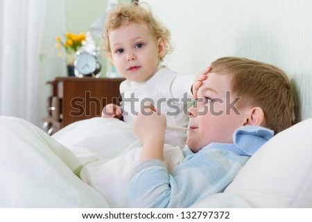 Little girl and her sick brother lying in bed at home