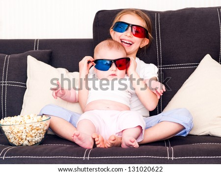 little girl and her sister  watching 3d TV