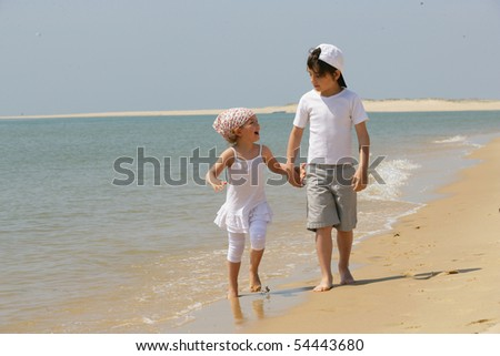 Little girl and little boy having a walk by the edge of the sea