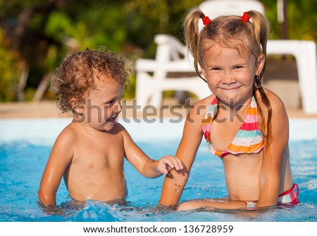 little girl and little boy sitting  in the swimming  pool